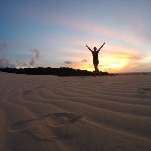 Mit erhobenen Armen durch den Sand laufend