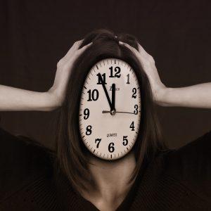 Frau hält ihren Kopf, der eine Uhr darstellt